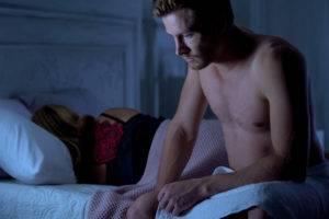 Nešťastný muž, spiaca žena v posteli